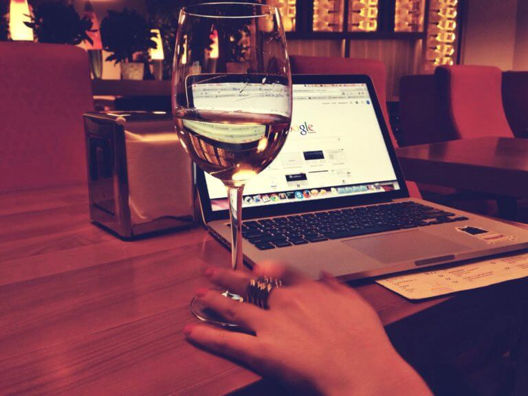 wine glass with laptop in the background